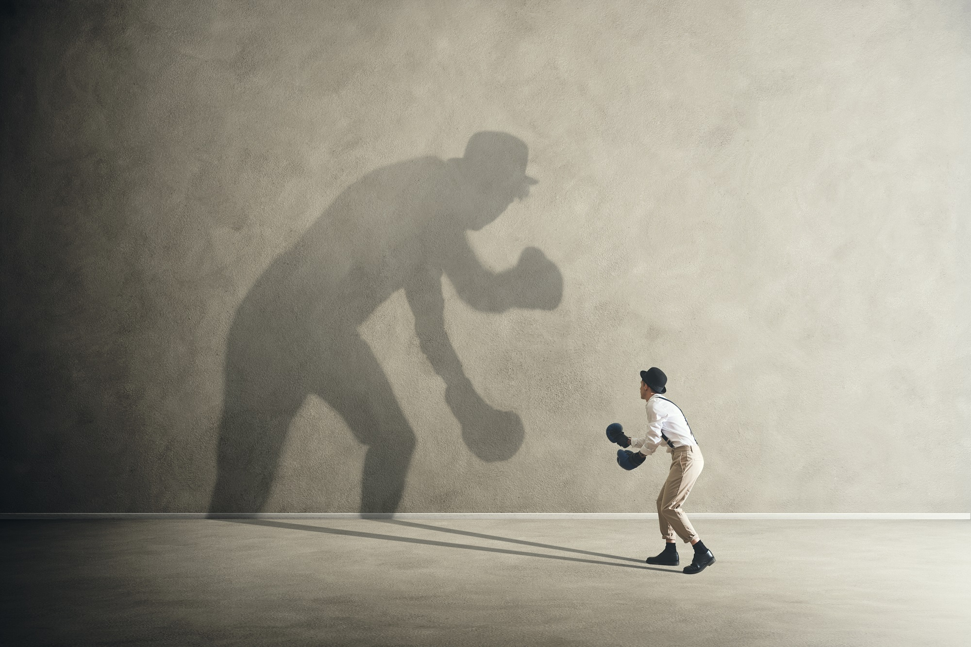Man boxing with his shadow