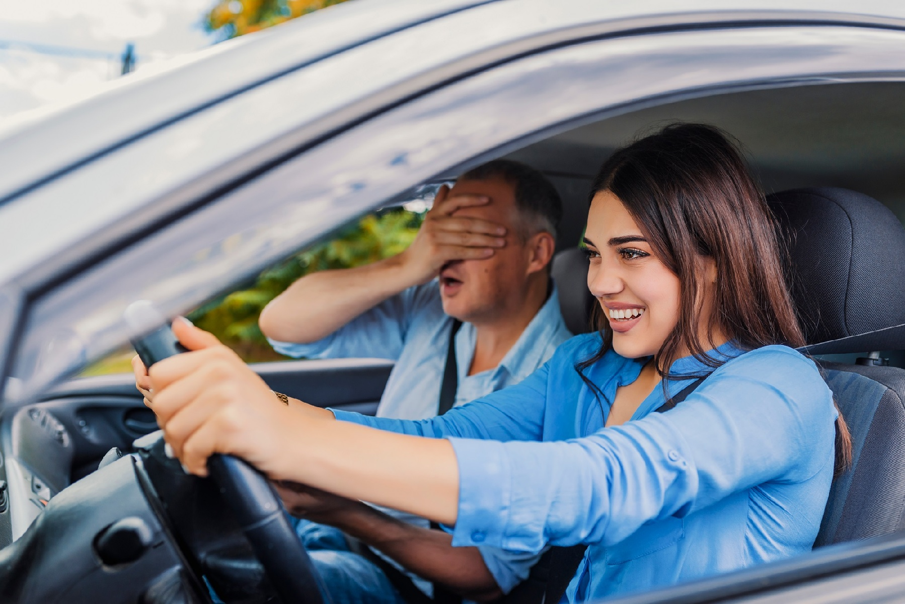 Dad covering eyes as daughter happily drives
