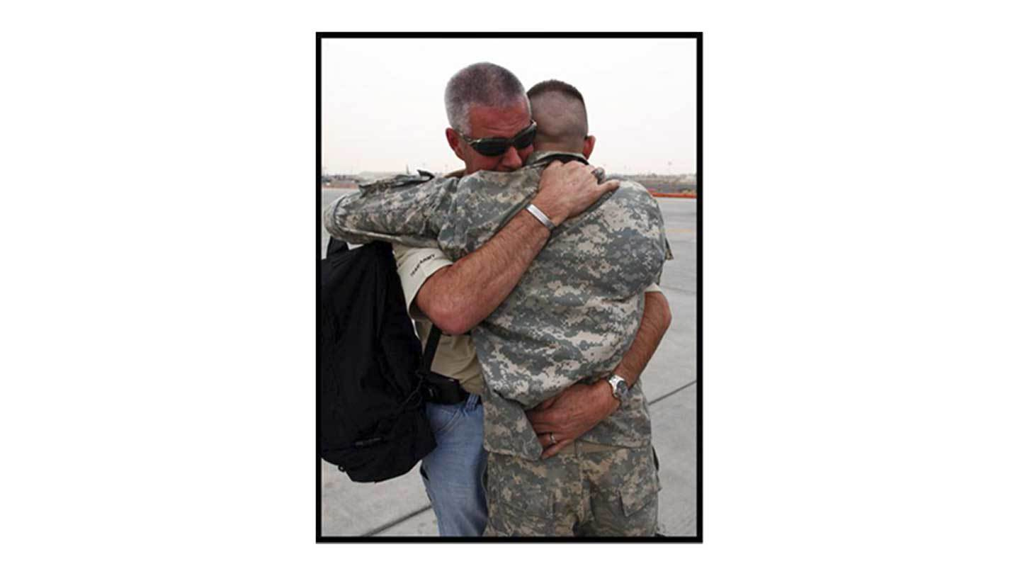 Army person hugging civilian