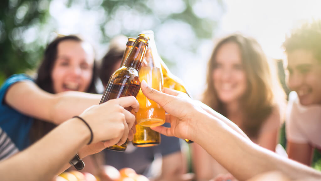 teens clinking beer bottles underage drinking