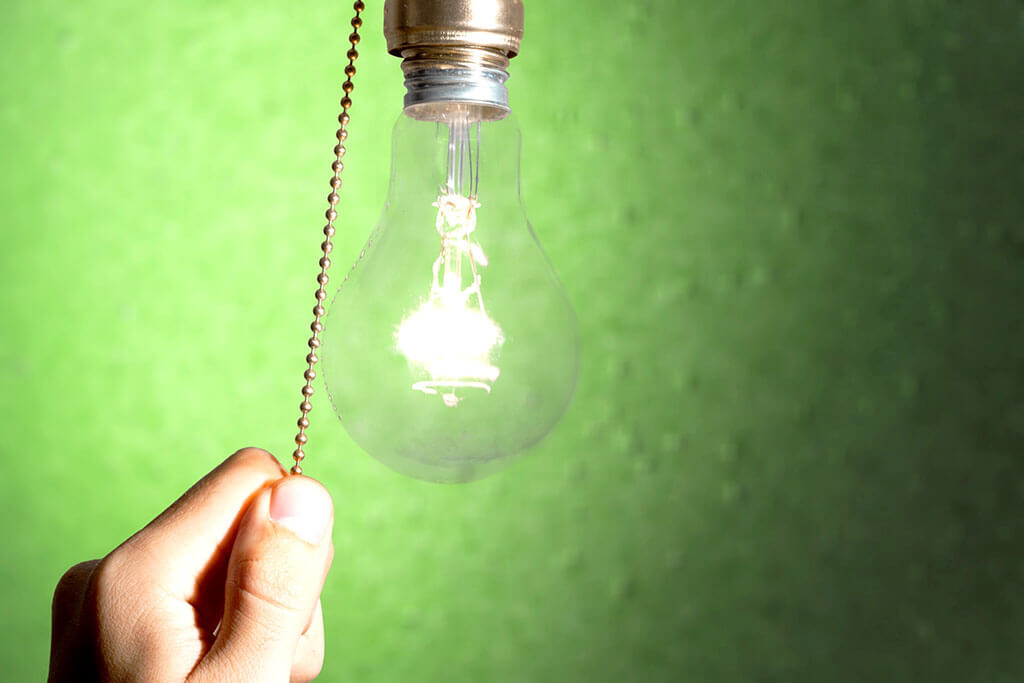 hand turning on lightbulb