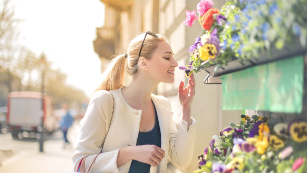 woman smelling flowers at an outdoor stand